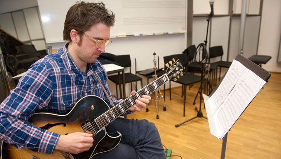 A music student sitting and playing an electric guitar.